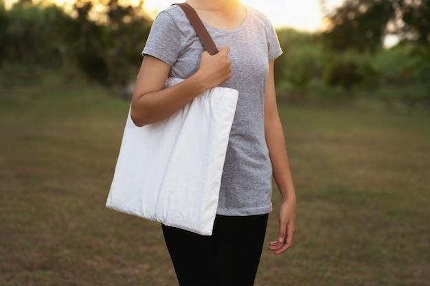 綿を保持している若い女性。エココンセプト