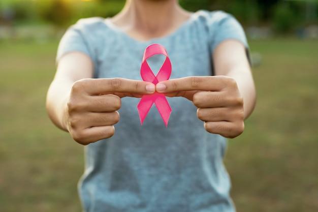 ピンクのリボンの乳房癌意識を持つ女性の手。コンセプトヘルスケア