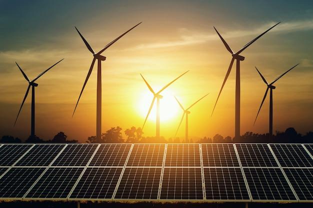 太陽電池パネルと夕日を背景にタービン