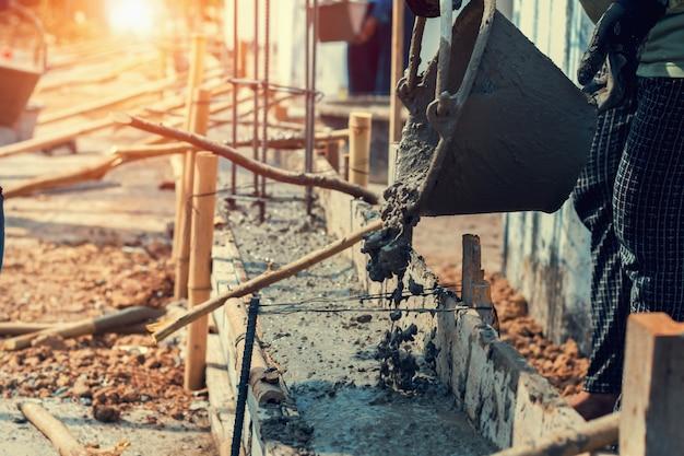 家を建てるための床に混合セメントを注ぐ労働者
