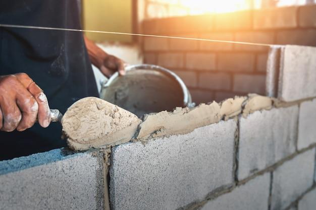 Рабочий строит стеновые кирпичи с цементом