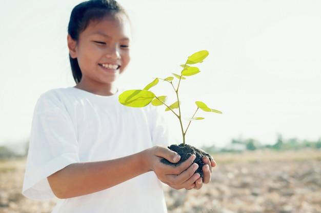 植栽のための若い木を抱えて笑顔の子供たち。コンセプトは世界を救う