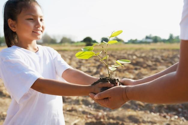 母親と子供たちが若い木を植えるのを助けます。コンセプトグリーンワールド