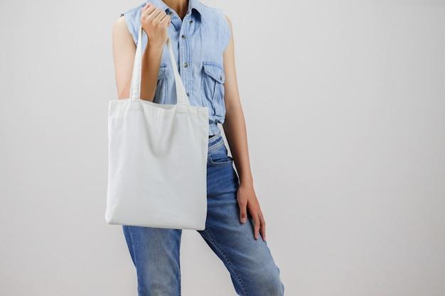 エコ布バッグを保持している女性を灰色の背景に分離します。