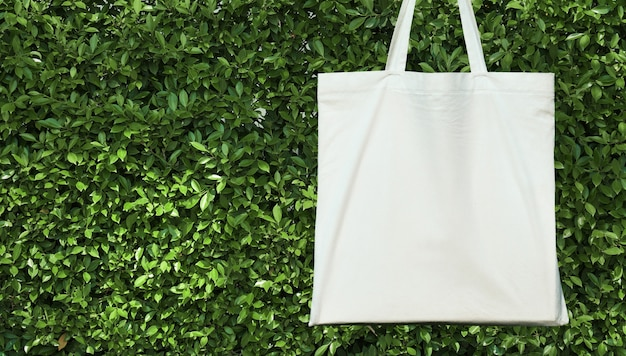 緑の葉の背景に空白の白いコットンバッグ。エコフレンドリーなコンセプト