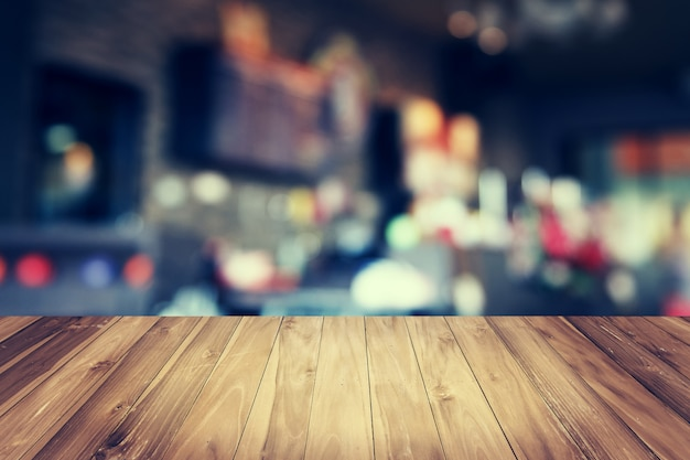 木製のテーブルとコーヒーショップの背景をぼかし