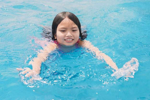 遊んでいる子供たちと幸せな笑顔でプールで遊んで