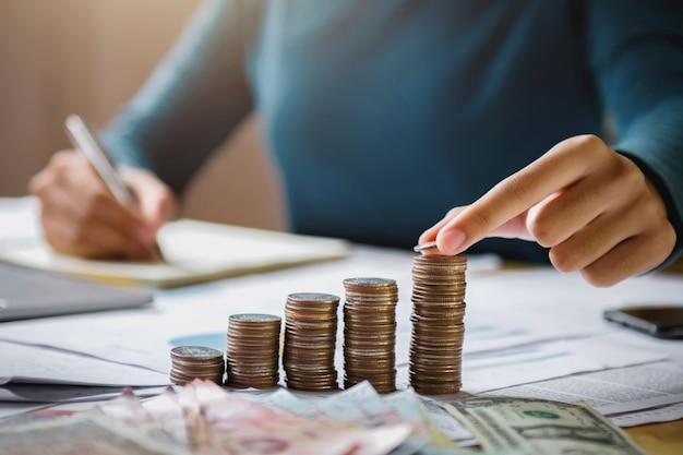 Рука бизнес-леди держа монетки для того чтобы штабелировать на финансах и бухгалтерии денег сбережений концепции стола