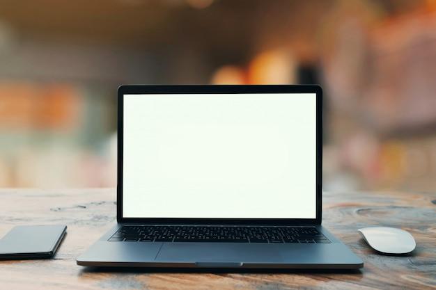 ラップトップコンピューター空白の白い画面とカフェ背景のテーブルに携帯