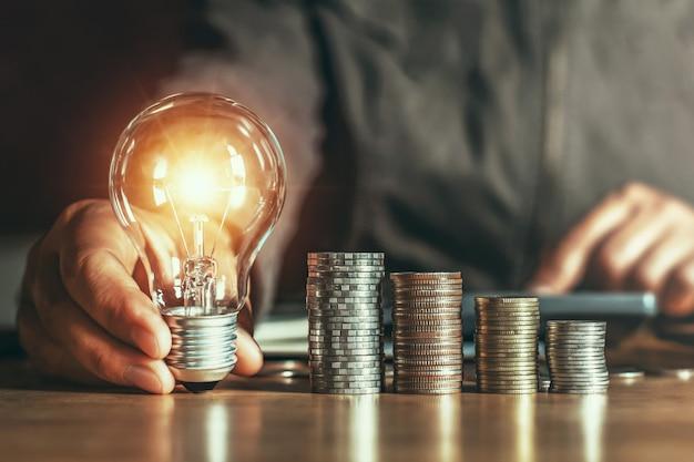 実業家の手持ち株電球。革新とインスピレーションを持つアイデアコンセプト
