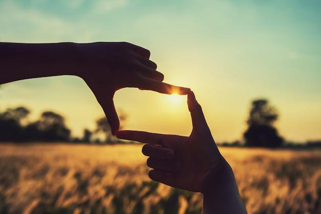 Люди делают руки, обрамляющие вид удаленного восхода солнца. бизнес-концепция