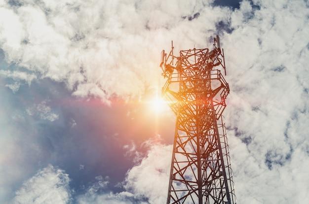 Телекоммуникационная башня с солнцем и голубым небом