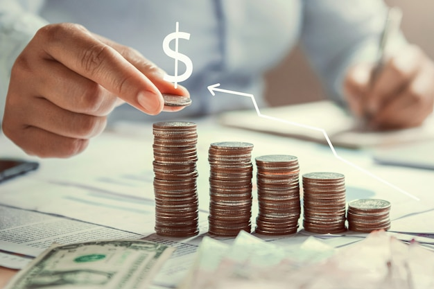 Рука бизнес-леди держа монетки для того чтобы штабелировать на финансах денег сбережений концепции стола