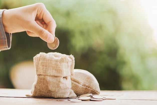 Рука кладет монеты в денежный мешок для экономии на фоне стола