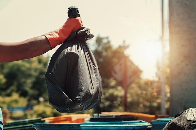 Рука, держащая черный мешок для мусора и кладущая в мусор