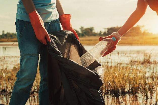 川での清掃のためのゴミプラスチックを拾う女性の手