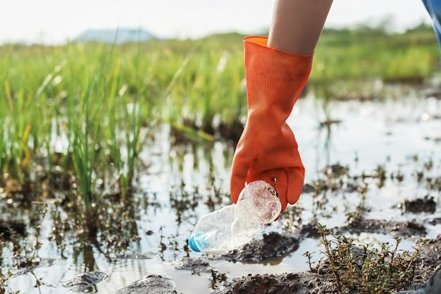 川の公園で清掃のためのゴミプラスチックを拾うボランティア女性