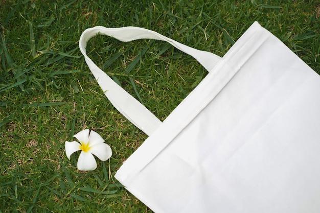 花と緑の芝生の背景に布バッグ