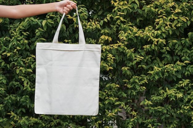 緑の葉の背景に布バッグを持っている手