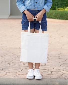 Молодая модель держит белую сумку для макета пустой шаблон