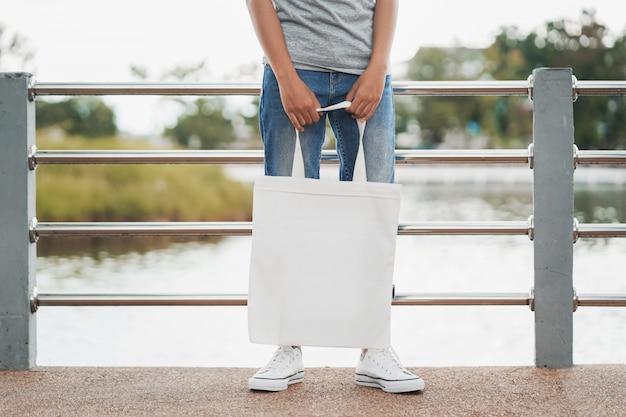 白い空白のトートバッグを保持している女性