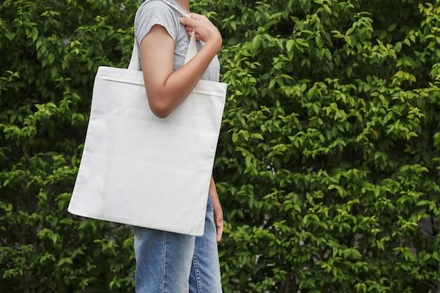 緑の葉の背景に白い綿のバッグと流行に敏感な女性