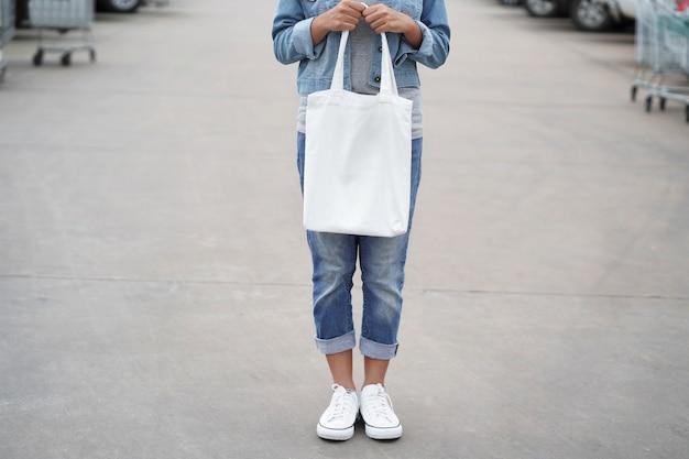 公園で白い綿のバッグを持つ流行に敏感な女性