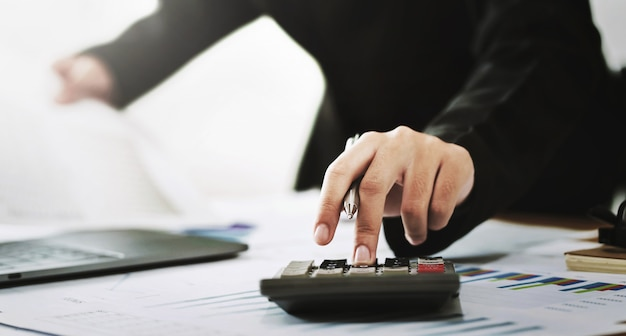 企業会計財務の概念。オフィスで働くラップトップで計算するための計算機を使用して会計士