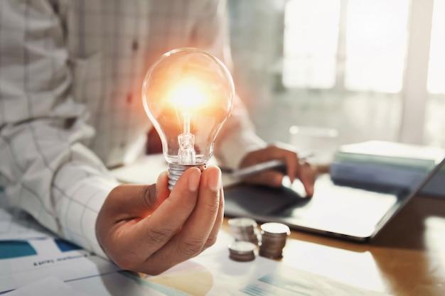 机の上のコインスタックと電球を持つビジネス女性の手。