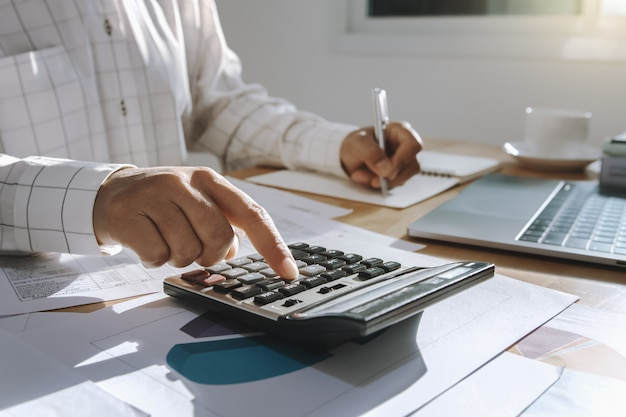 Коммерсантка работая на столе в офисе и используя калькулятор и компьтер-книжку с ручкой для вычисляет