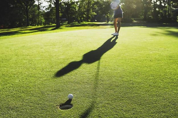 ゴルフプレーヤーがゴルフボールを穴に入れて