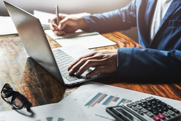 オフィスの机の上のラップトップを使用して作業する実業家。