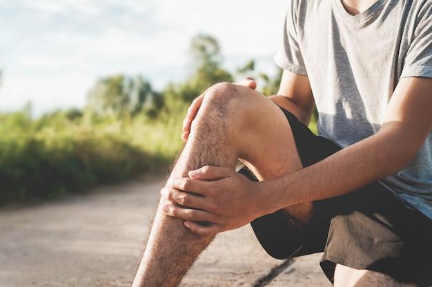 運動で負傷した男性、彼の手を使って公園で膝を抱える