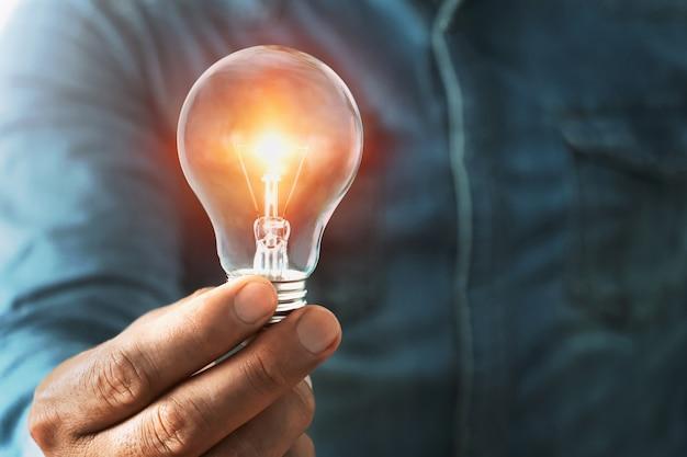 Рука бизнесмена держа лампочку с солнечностью.