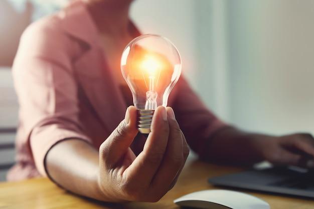 オフィスでラップトップを使用して電球を持っている手。コンセプト省エネ電力
