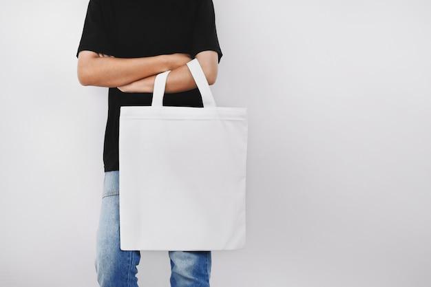 エコ生地のバッグを保持している流行に敏感な女性