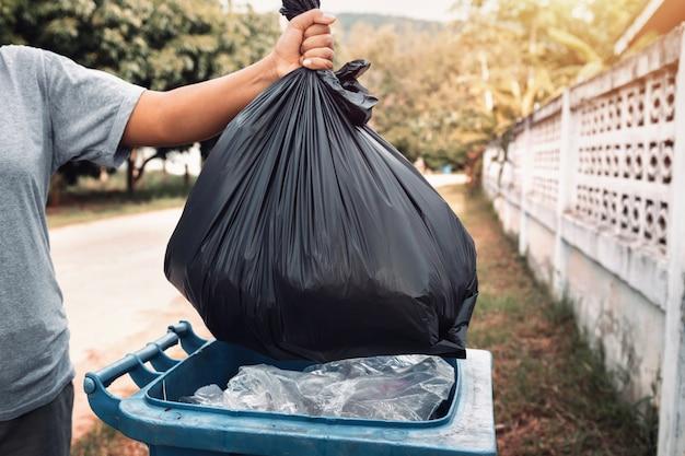 ゴミを掃除するための黒い袋にゴミを持つ女性の手