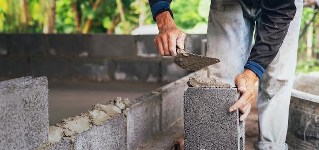 建設現場でレンガの壁にセメントを左官工事労働者の手