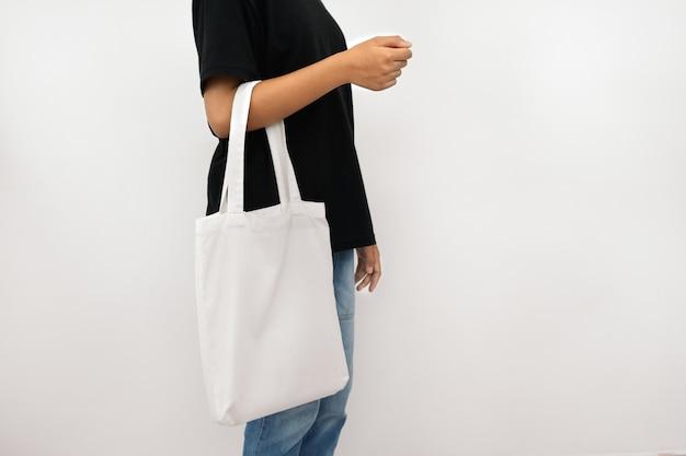 Молодая женщина, держащая эко хлопок сумка изолировать на белом