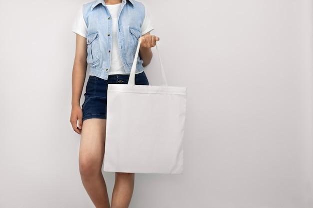 Молодая женщина, держащая эко хлопок сумка на стене белый