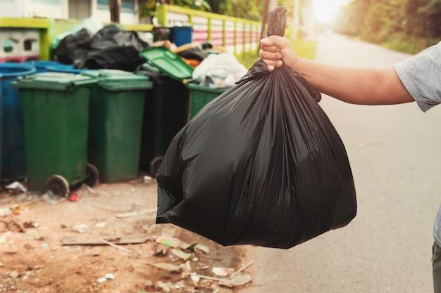 Женская рука держит мусор в черной сумке для уборки в мусор