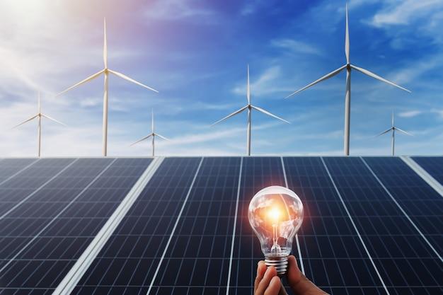 ソーラーパネルと風力タービンの背景を持つ電球を持っている手。自然界のクリーンエネルギー