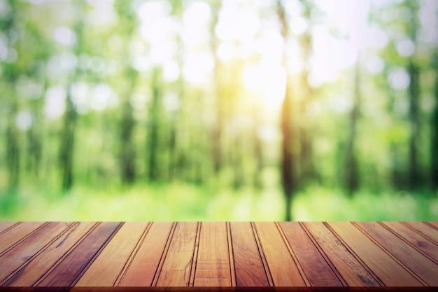 空の木製テーブルに森の背景をぼかし