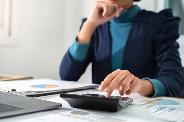 Коммерсантка работая используя калькулятор и компьтер-книжку в офисе. концепция финансов и бухгалтерского учета