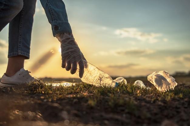 公園での清掃のためのゴミ瓶を保持する手。エココンセプト