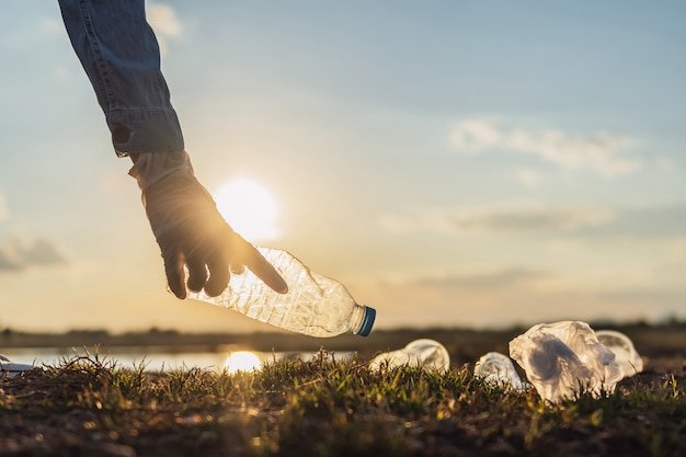 朝の光で公園で掃除のためのゴミ瓶を保持する手。エココンセプト