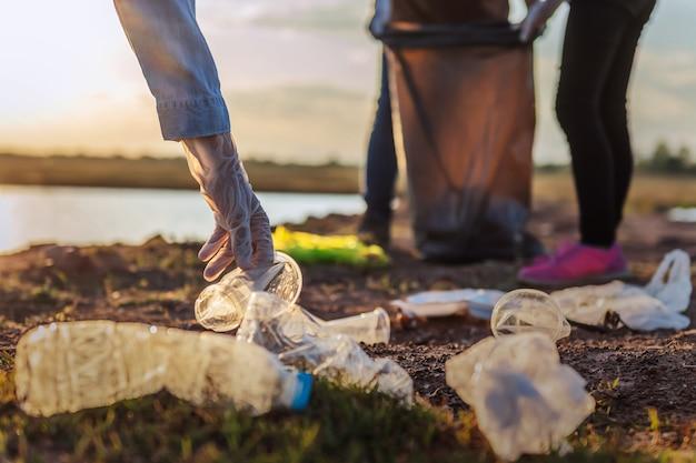 日没で川の近くの公園でゴミ袋を黒い袋に入れてボランティアするボランティア