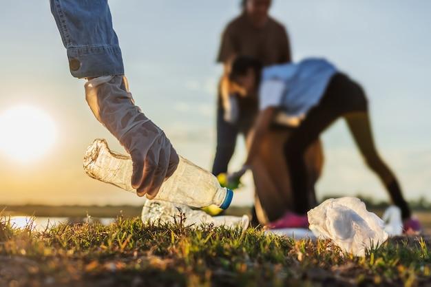 日没で公園の川でゴミ袋を黒い袋に入れてボランティアする人々