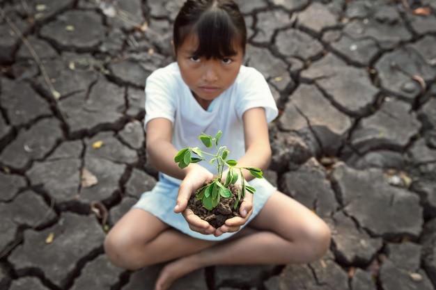 若い植物を保持している亀裂の地面に座っている子供たち。コンセプトセーブワールド