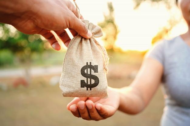 コンセプト財務会計。女性のためのお金の袋を与える手